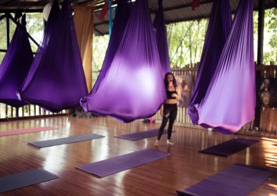 yoga students hanging covered in and with aerial yoga swings