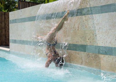 Amber Hagberg doing yoga under waterfall in pool at Danyasa